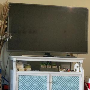 """Photo of Samsung 55"""" UHD Smart TV along with stand beautifully decorated"""