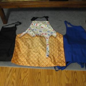 Photo of 11 Aprons * 5 Blue * 5 Black * 1 Looks Like A Ice Cream Cone