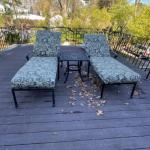 Two cast aluminum chaises with cushions and side table