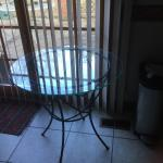 Brand new outdoor glass top table with wrought iron base and legs