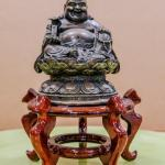 Bronze laughing Buddha on cherry wood stand