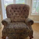 Large tan & black tufted reclining chair with wooden claw feet.