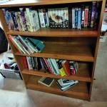 LOT 293 WOOD BOOKSHELF WITH VHS AND BOOKS