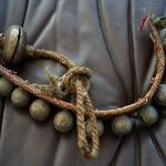 BRASS MIDDLE EASTERN ENGRAVED BELLS ON WOVEN CLOTH ANTIQUE